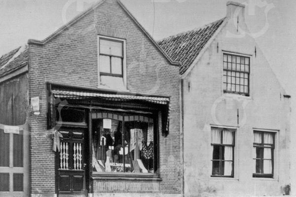 F0712 <br /> Manufacturenzaak van wed. Noordermeer aan de Hoofdstraat met een heel oud woonhuis. Beide panden zijn gesloopt in augustus 1931 en vervangen door een nieuw dubbel winkelpand met bovenwoning. Sinds december 1999 is hier Eetcafé de Voogd. Foto: jaren '20.