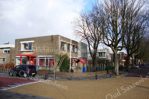 F2381<br /> De hoek van de Menneweg en de Rusthofflaan. Op deze hoek was vroeger de boerderij van Chris van der Voort. Na 1966 werd daar het politiebureau gebouwd. Dat is nu al enige tijd niet meer als zodanig in gebruik; nu is hier de kinderopvang Small Steps.  Rechts erachter (in de Rusthofflaan) staat nu een gezondheidscentrum.