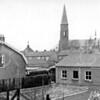 F0717 <br /> St. Pancratiuskerk met daarvóór de huizen aan de Parklaan. Links het laatste huis in de Floris Schoutenstraat. Rechts het bedrijfspand van Homan en daarachter een stukje van het dak van de boerderij van Piet Langeveld. Op de voorgrond staat nu een gezinsvervangend tehuis. De foto is gemaakt vanaf Floris Schoutenstraat 40. Foto: 1960/1962.