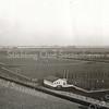 F0897 <br /> Luchtfoto van de vroegere sportvelden met de clubgebouwen, met op de achtergrond de Kagerplassen. Vlak achter de voetbalvelden is in de verte van links naar rechts rijksweg A44 te ontwaren. Het voorste gebouw is van de tennisvereniging, het achterste van de voetbalverenigingen Teylingen en Ter Leede. Dit hele gebied is thans volgebouwd met de woningen van het Mennepark, behalve het terrein van rugbyclub The Bassets. Foto: 1951.