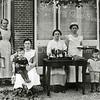F0953 <br /> Het personeel en de kinderen van dokter Le Grand. De foto is aan de achterkant van het huis aan de Hoofdstraat genomen. V.l.n.r.: Maartje Oudshoorn en Lena Overvliet met Wally le Grand op schoot. De andere personen zijn niet bekend.  Maartje Oudshoorn huwde met Gijs Overvliet sr. en Lena Overvliet met Gerrit van der Voort (zie F0954). Foto: vóór 1917.