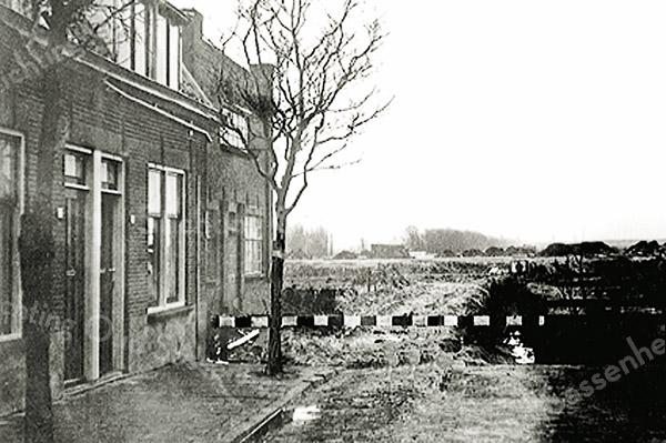 F3913<br /> De voorheen doodlopende Bijdorpstraat had aan het einde een hek, waarachter een sloot lag.<br /> In het voorjaar van 1960 is de sloot door een duiker vervangen en is de straat doorgetrokken tot de huidige Narcissenlaan. Links op de foto staan de laatste huizen van de Bijdorpstraat en de achterzijde van de bollenschuur van Vos. Op de foto wordt de riolering aangebracht en de grond bouwrijp gemaakt. Het geblokte hek stond op de plaats van het oorspronkelijke hek. Foto: 1960.