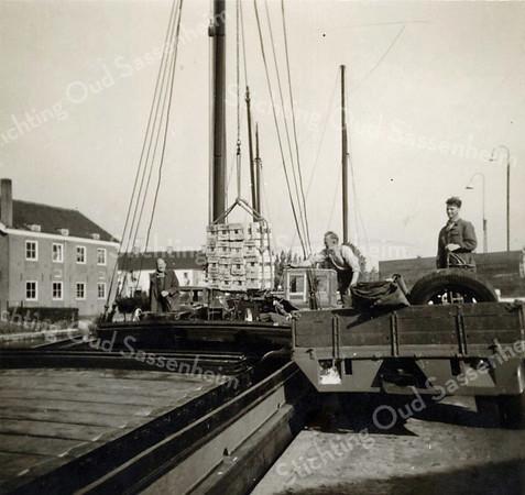 F3591<br /> Links staat schipper Tinus van der Hoorn die een lading tegels voor tegenhandel Zwaan op een vrachtauto laadt. Aan de linkerkant staat  de oude schuur van fa. Kruijff.