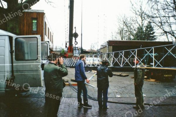 F3855<br /> De bouw van een 45 meter hoge zendmast voor mobilofoon- en portofoonverkeer van de politie. Deze zendmast werd gebouwd door de PVD (politie verbindings- dienst)<br /> De vakwerkmast bestond uit 5 delen van 8 meter die hier worden geplaatst. De hele constructie stond op een grote betonnen klomp met heipalen in de grond van 11 meter lang. Bovenop stond ook nog een zendgedeelte van 2,5 meter hoog. Van af de grond was het bouwwerk 45 meter.<br /> Deze mast verving een 17,5 meter hoge kantelmast die een paar jaar eerder was geplaatst.<br /> <br /> Het 'houten' gedeelte van het gebouw was niet oorspronkelijk. Het was wel degelijk van steen maar<br /> dan met een houten buitenkant. Het werd later toegevoegd voor een uitbreiding omdat het bureau<br /> te klein werd. het werd nl. gebruikt als regiobureau voor de Duin- en Bollenstreek van de Rijkspolitie.