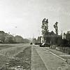 F0977 <br /> Hoofdstraat, gezien vanuit  noordelijke richting. Wat verkeer betreft geeft Sassenheim-noord een uiterst rustig beeld. De tramrails zijn al verwijderd. Links zien we villa Hyacintha. De auto links komt net vanaf de Van Pallandtlaan.  Rechts achter de heg het braakliggende stuk land tussen de villa De Schulp en de Carolus Clusiuslaan, die net voor de gebouwen geheel rechts aansluit op de Hoofdstraat. Foto: ca. 1951.