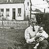 F1912 <br /> Foto van boerderij Jagtlust aan de Warmonderdam. De boerderij stond – vanaf de Hoofdstraat/Rijksstraatweg gezien – aan de linkerkant van de weg (nu Warmonderweg, vlak voor de rotonde). <br /> Op de voorgrond zit Van der Elst (vader van Fons v.d. Elst) met dochtertje Riet.