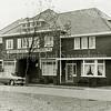 F0880 <br /> Bedrijfspand van de Sassenheimsche Motorreederij N.V. Wesseling, geflankeerd door twee woonhuizen aan de Molenstraat in later jaren. In vergelijking met de foto uit 1934 (F0879) en 1945 (F0881) staan er hoge bomen voor het pand, er zijn vlaggenstokken geplaatst en er is een straat aangelegd. Foto: 1975?