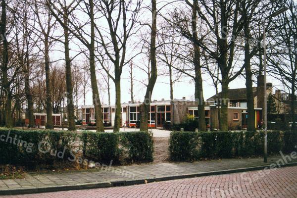 F0242 <br /> De chr. kleuterschool De Zonnebloem aan de Charbonlaan (nu Willibrorduslaan), tegenover basisschool De Overplaats. Het schoolgebouw was niet bedoeld voor gebruik voor een langere tijd. Na de sloop in ca. 1990 bleek de grond onder de school sterk vervuild te zijn en moest eerst worden gereinigd. Daarna kon op dit terrein en al het grasland links ervan het nieuwe gemeentehuis worden gebouwd. Foto: 1988.