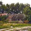 F0064 <br /> De boerderij van W. van Rijn, gezien vanaf de Carolus Clusiuslaan. Op deze foto het zicht op de stal, hooiberg en de schuur. De houten afzetting, het zware geboomte en het naastgelegen bollenland maken het plaatje compleet. Foto: 1979.