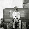 F0340 <br /> Henk Perfors op de reserveband van de Ford van W. van Zonneveld voor diens huis op de hoek Hoofdstraat/Zuiderstraat. Links het café van Adriaan Schrama met het bord 'Vollenhoven's Bieren'. Foto: ca. 1922.
