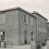 Fcs0123<br /> Hygia aan de Menneweg, Het voorste gedeelte was v.h. de bollenschuur van Janus Schoo (een uit Noord Holland afkomstige bollenkweker) de originele ramen en deuren van de bollenschuur zijn nog aanwezig. Het hogere achterste gedeelte is in 1948 gebouwd, en het voorste gedeelte is later in twee fasen verbouwd tot het huidige --pand en nu (2007) is het geheel in gebruik als kinderdagverblijf. In de deuropening staat Henk Langelaan, deze foto is van begin 50er jaren.