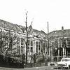 F0289 <br /> Op deze plek is nu het dorpsplein vóór de Dorpskerk. Het Verenigingsgebouw (links) van de Ned.-herv. gemeente aan de Hoofdstraat. In 1866 gebouwd als openbare school en als zodanig tot 1923 gebruikt. Daarna werd het een hervormde school tot 1930. Op 14 december 1931 werd het in gebruik genomen als Vereenigingsgebouw der Ned. Herv. Gemeente. In 1967 is het gebouw gesloopt. Rechts het woonhuis (ook uit 1866) van het hoofd der school. Vanaf 1881 woonde meester J. Beumer daar en vanaf 1926 meester A. den Haan. Ook dit pand werd in 1967 gesloopt. Vóór 1866 stond hier overigens ook al een onderwijzerswoning met een schooltje. In 1813 woonde meester A. Allaries daar en was het schooltje in gebruik.   Foto: vóór 1967.