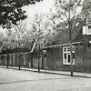 F0683 <br /> De J.P. Gouverneurlaan met de viswinkel van Nic. Roos. De winkel is gesloopt in 1964.  Later kwamen er panden van een financiële instelling, makelaar De Leeuw, Decorette en een modewinkel. Daarboven kwamen appartementen. Links daarnaast kwam de Rabobank, die inmiddels is verhuisd naar de Hortuslaan. Foto: begin jaren '50.
