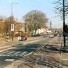 F4273<br /> <br /> De Hoofdstraat, gezien richting centrum ter hoogte van Mecklenburg. Links de bebouwing van de Postduif; de gebouwen van kistenfabriek M. Bakker en de RK Pancratiuskerk op de achtergrond. Foto: 2003