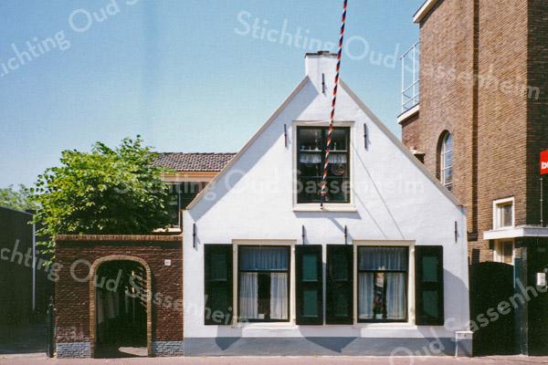 F0066 <br /> Een van de oudste huizen van Sassenheim, aan de Hoofdstraat nr. 205 wordt bewoond door schilder Van Goeverden. Het is prachtig opgeknapt. De luiken zijn weer aangebracht en met het karakteristieke poortje en de leilinden langs het straatje is het een sieraad voor het dorp. Rechts het pand van Cor van Goeverden, de kruidenier. Thans (2016) boekhandel The Read Shop. Foto: 1995.