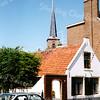 F0067 <br /> Het eeuwenoude pand van de fam. Van Goeverden aan de Hoofdstraat nr. 205, nu van terzijde gezien met daarboven de toren van de Ned.-herv. kerk of Dorpskerk. Foto: 1995.