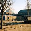 F4338<br /> Een lege plek in de Kerklaan, waar voorheen een rij huizen heeft gestaan. Op de achtergrond de flat 'Sassemerhof'. Rechts de aardewerkfabriek 'Velsen'. Foto 2002