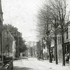 F0376 <br /> De Hoofdstraat benoorden de Klapbrug, gezien vanuit het noorden richting centrum. Links het huis van de fam. Jan Blom, gebouwd in 1872.  Daarvoor woonde hier Cornelis Rhijnsburger. Rechts de latere bakkerswinkel van Rhijnsburger. De man met oliekar en hond is Gerrit Dannijs, de vader van Clemens Dannijs. Later werd hij de bekende fondsbode. Hij riep dan aan de deur: 'de fondsenbooi' of 'de ziekenfongst'. Het witte huis links stond op de hoek van de Kastanjelaan. Dit werd in 1929 afgebroken. Zie ook 'Sassenheim in oude ansichten' van G. Verschoor, pag. 72. Foto: ca. 1900.