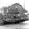 F3944<br /> De Zandsloot ten oosten van de Postbrug. Het huis achter de schuit was van Cornelis van der Wiel en staat er nog. Het wordt nu bewoond door de familie Langeveld. Rechts daarvan zien we het witte huis Hoofdstraat 100 van de heer Wim Van Hage. De lading die ze lossen zijn veekoeken, de handel van Cornelis. Het kleinste mannetje midden op de schuit is Jaap van der Wiel en helemaal rechts staat zijn vader Cornelis van der Wiel. Foto: 1910