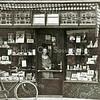 F1824 <br /> De sigarenwinkel van mevr. Omzigt. Achter de deur staat haar pleegdochter. Na een grondige verbouwing van dit pand en het slopen van het lage pand van de dames Van Hoekelen ernaast vestigde zich hier de bloemenzaak van Preenen. Foto:  jaren '30.