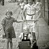 F0222 <br /> Foto uit 1943/44, genomen in de Hoofdstraat bij de huizen van Melman. In de wandelwagen zit Frans Jonker, geboren in 1942 (ca. 1½ jaar oud), zoon van Arie Jonker en An Waasdorp. Naast de wagen Toos Jonker, nichtje van Frans Jonker. Meisje achter de wagen is Lenie Waasdorp. Foto: ca. 1943.
