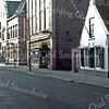 F0283 <br /> De Hoofdstraat in het centrum aan de westkant. Rechts het woonhuis van schilder Kees van Goeverden, één van de oudste panden van Sassenheim, inmiddels helaas gesloopt. Het grote pand daarnaast was eerder het woonhuis van dokter Hueber. Op de foto is het 't pand van fa. G.Lascaris en het is begin jaren '80 gesloopt. Op dezelfde plaats is een nieuw pand gebouwd voor Blokker en de Schoenenreus, was eens het woonhuis van dokter Hueber. In 1955 kocht Lascaris het pand en in 1979 hield hij ermee op. Uiterst links het postkantoor, gebouwd in 1902, nu (2016) Terstal. Foto: 1979.