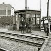 F2287<br /> S.L.J. van der Kraan bij het bedieningsrad waarmee de spoorbomen werden op- of neergelaten. Deze handbediende spoorbomen werden de langst gebruikte in Nederland. Van der Kraan staat voor het wachthokje bij de spoorwegovergang Klinkenberg. Links van de foto is later - in 1939 - de Sikkens' Lakfabrieken N.V. gevestigd. In het bollenland achter het huis links op de foto (Rijksstraatweg 39) is in 1943 een vuurstenen sikkel gevonden. Deze foto is van19 juni 1932.