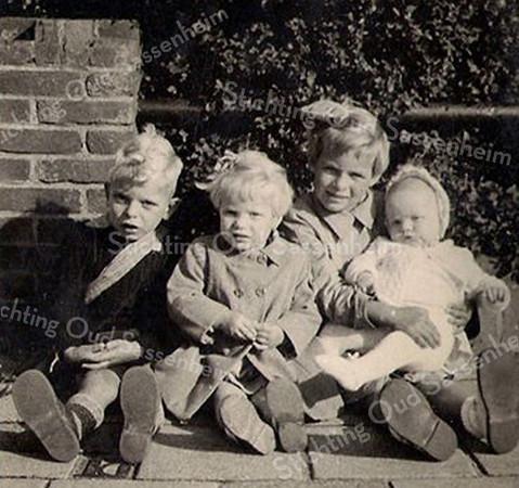 F3971<br /> Kinderen Van der Elst zitten hier tegen een muurtje aan de Charbonlaan. Ze zijn onderweg naar de kermis en zijn hier even gaan zitten voor de foto. Vlnr: Theo met oranje sjerp, Paulien en Riet met oranje strik en Ada op schoot bij Riet. Foto: 1956