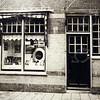 F4544<br /> De fotozaak van Turk in de Floris Schoutenstraat, nr. 21. De grootvader van Cees Turk is de zaak begonnen in de Tijloosstraat. Later is de winkel verhuisd naar de Floris Schoutenstraat, daarna de Charbonlaan nr. 1, uitgebreid met het pand Charbonlaan nr. 2. In de 70er jaren zijn ze verhuisd naar het pand aan de Hoofdstraat naast Duynstee, waar de winkel nu nog is gevestigd.