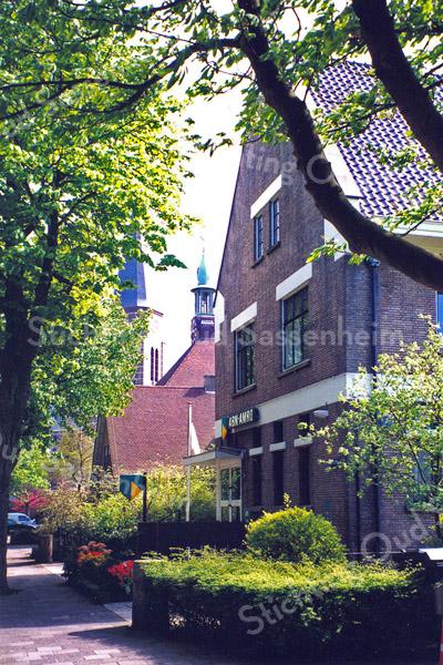 F0504<br /> Het bankgebouw ABN Amro (voorheen de Twentsche Bank) aan de Wilhelminalaan nr. 5. Verder is het voormalige raadhuis te zien (nu Sikkens Experience Centre), met de toren van de St. Pancratiuskerk op de achtergrond. De foto is genomen kort voordat het bankgebouw werd verbouwd. De ABN Amro is inmiddels verplaatst naar Hoofdstraat 213. Op 7 juni 2013 werd het pand op de foto geopend door het Veteranen Ontmoetings Centrum Duin- en Bollenstreek. Sinds 2016 is deze stichting verhuisd naar een ander pand aan de Hoofdstraat nr. 292, naast de moskee Al Imaan. Anno 2016 is er een kantoor gevestigd in het pand op de foto. Foto: 1999.