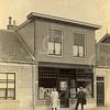 F0765 <br /> Op de foto zien we van links naar rechts Hoofdstraat 55, 57 en 59 (oude huisnummering). Op nummer 55 woonde de fam. G. Buurman. In 1918 kocht W. Zijerveld het winkelpand (nr. 57) en het pand rechts (nr. 59). De winkel in kruideniers- en grutterswaren werd inwendig met het woonhuis ernaast verbonden en het werd één adres. De panden staan er nog steeds, nu op Hoofdstraat 101 en 103. <br /> Opmerkelijk is dat de fotograaf een voorkeur had om zijn opnamen te verlevendigen met daar wonende of willekeurige personen. Foto: vóór 1919.<br /> <br /> [Collectie Oudshoorn 082: W. Zijerveld, Oude Post. Hoofdstraat 57 volgens oude nummering.]