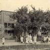 F0770 <br /> Het kantoor, bollenhuis en de pakkerij van A. Frijlink & Zonen aan de Zandslootkade. Op de voorgrond een grote groep kinderen en enkele volwassenen. Het bedrijf werd overgeplaatst naar Noordwijkerhout en na afbraak van de gebouwen verrees hier in de jaren '80 de Prins Clausstraat. Foto: vóór 1921.<br /> <br /> [Collectie Oudshoorn 059: kantoor bollenhuis en pakkerij, Zandslootkade A. Frijlink & Zn. 1911.]