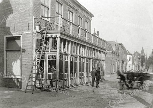 F0802 <br /> De timmerman is bezig met het zagen van latwerk voor de pas aangebouwde serre van hotel-café-restaurant 't Bruine Paard aan de Hoofdstraat. Een man die een kar trekt komt uit de Kerklaan. Daarachter zien we de panden van Van der Meer, Van Niekerk, kantoorboekhandel De Gruijter, het uitspringende zusterhuis en in de verte het hoge pand met torentje van H.A. de Leeuw, later sigarenwinkel B. van Loo en nu Heemborgh Makelaars. Foto: vóór 1921.<br /> <br /> Collectie Oudshoorn 025: Bouw van een serre C. Schippers 1901.