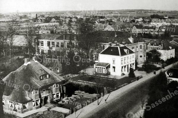 F2750<br /> Een luchtfoto van de Hoofdstraat te Sassenheim. Het witte pand in het midden is huize West-End. Aan de  rechterkant van West-End staat het St. Annaklooster, met daarachter de r.-k. meisjesschool St. Anna. De school is afgebroken; op ongeveer die plaats staat nu (2017) de Vomar.