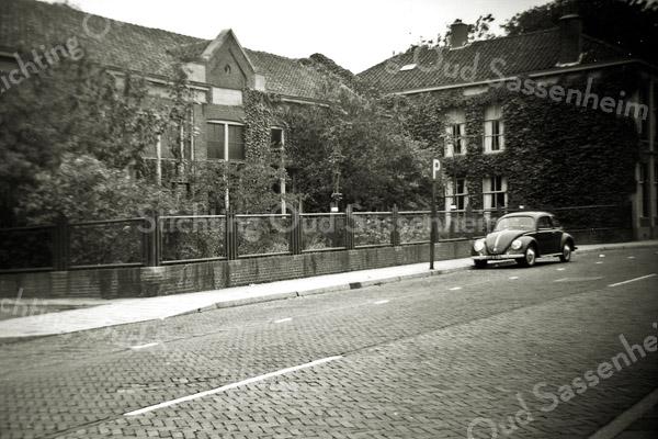 F0471 <br /> Het Verenigingsgebouw van de Ned.-hervormde gemeente aan de Hoofdstraat, met rechts het woonhuis van meester A. den Haan. Het Verenigingsgebouw en het woonhuis werden afgebroken in 1967. Nu is hier het dorpsplein vóór de Dorpskerk. Op de voorgrond een Volkswagen (kever).