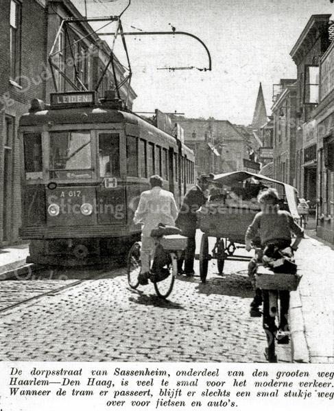F0204 <br /> De dorpsstraat van Sassenheim in 1936, ter hoogte van waar nu (2016) de winkel van bakker Ammerlaan is. Het eerste wat hier opvalt is de elektrische tram. De groenteman met paard en wagen staat geparkeerd. Een fietser moet ertussendoor zien te komen. De straat is geplaveid met kinderhoofdjes. Er was vroeger veel minder verkeer, maar de fietsers moesten terdege rekening houden met de tramrails. Foto: 1936.