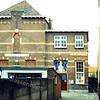 F0250 <br /> De oude St. Pancratiusschool aan de Hoofdstraat, gebouwd in 1902/03. Op de witstenen rand in het linkerdeel van de voorgevel was de naam van de school te lezen, die dus evenals de kerk gewijd was aan St. Pancratius. In 1948 ging de opleidingsschool St. Antonius in hetzelfde pand van start. Deze vierklassige school betrok in 1950 het nieuw gebouwde schooltje op de hoek Parklaan/St. Antoniuslaan. In 1956 werden beide scholen samengevoegd en gingen verder als St. Antoniusschool. In 1959 werden alle leerlingen weer in de school op de foto verenigd. In 1981 verhuisde de St. Antoniusschool naar de Knorrenburgerlaan en heet sinds 1985 De Kinderburg. <br /> Hier staat de school al weggedrukt tussen het pand links van de VSB-bank en rechts de woninginrichting van Van der Meer. Nu (2016) staan daar links de kledingzaak 'Forty four and more' en rechts de hengel- en watersportwinkel Ahoy. Het muurtje en schuurtje links staan er nu nog steeds!<br /> Het schoolgebouw is gesloopt in 1984. Het pad is blijven bestaan en vormt een verbinding voor voetgangers en fietsers tussen de Hoofdstraat en de Keerweerlaan. Foto:  midden jaren '60.