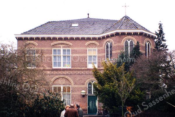 F0381 <br /> Aan de Hoofdstraat: het vroegere St. Annaklooster en de St. Annaschool voor meisjes, hier nog in gebruik als onderkomen voor verschillende verenigingen. Een deel van de voormalige school is inmiddels gesloopt, maar het voorste gedeelte – het voormalige klooster – is grotendeels gespaard. Achter de fraaie voorgevel is nu supermarkt de Vomar. Rechts boven met het kruis op het dak was de voormalige kapel. Zie ook' Sassenheim in grootmoeders tijd' pag. 35. Foto: 1997.