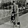 F2695<br /> Cor van der Elst staat hier op het fietspad langs de Rijksstraatweg, tegenover de Warmonderdam en café Juffermans. Het is bollentijd, gezien de slingers die over het hek hangen.