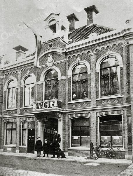 F1186 <br /> Het oude gemeentehuis of raadhuis aan de Hoofdstraat. Gebouwd in 1871 en in 1913 inwendig verbouwd. Het gebouw deed dienst tot 31 december 1929. Daarna werd het nieuwe raadhuis aan de Wilhelminalaan in gebruik genomen. Reeds vele jaren is hier nu de winkel voor mannenmode van Melman gevestigd. Foto: 1929.