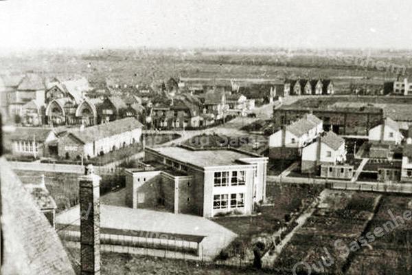 F2294<br /> Foto genomen vanaf de St. Pancratiuskerk. In de verte gezicht op de Menneweg. Het schoolgebouw in het midden is de r.-k. Don Bosco Mulo. Links daarvan staat de Dr. De Visserschool voor prot.-chr. mulo; het laatste gebouw heet nu (2016) Kastanjehof. Beide scholen staan aan de St. Antoniuslaan. Rechts op de foto (het donkere gebouw) staat een bollenschuur van Baartman & Koning. Op deze plaats is nu De Hooge Wei. Zie ook tekst bij G1076.