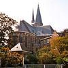 F1837 <br /> De St. Pancratiuskerk, gezien vanuit het noordoosten, zoals de kerk eruit ziet sinds de totale herbouw van 1913-1929. De kerk en pastorie (1870) behoren tot de gemeentelijk monumenten. Foto: 2000.
