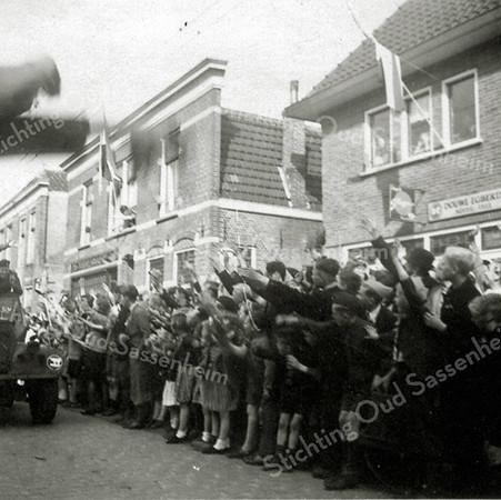 F0362a <br /> De intocht van de Canadezen  met zwaaiende mensen tijdens de bevrijding in mei 1945. Foto genomen in de Hoofdstraat, ter hoogte van de Kerklaan. Rechts is de kruidenierswinkel van Kaptein te zien met daarnaast de smederij van Bruijnen. Foto: 1945.<br /> .
