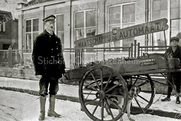 F2686<br /> Petroleumboer Jaap Oudshoorn (1886-1952) met zijn hondenkar. De foto is genomen is voor het Verenigingsgebouw aan de Hoofdstraat, naast de winkel van Mathôt. Oudshoorn had zijn bedrijfje aan de Kerklaan.