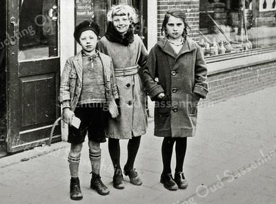 F0076 <br /> De foto is genomen voor de wagenmakerij van Koos Bakker aan de Hoofdstraat. Achter de schuifdeur een bordje waarop staat: 'Uw hulp noodig! Steunt het'. De kinderen op de foto zijn v.l.n.r.: Gerrit van Harskamp (bekend voetballer), Celia van Harskamp en Jannie Hogewoning. Foto: ca. 1935.