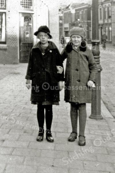 F2939<br /> Twee meisjes op de Hoofdstraat ter hoogte van het huis van meester den Haan, nu ter hoogte van het dorpsplein bij de Dorpskerk. Het linker meisje is Reina Geerling, het rechter meisje Rie Faas. Op de achtergrond rechts het huis van Vlasveld en links daarvan het pand van Bruijnen. Ook is nog de elektrische klok te zien van Jamin. Links het pand van kapper de Jong. Foto is van ca. 1932.