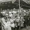 F3185<br /> De uitvoering van de Kleppermarsch op 17 september 1913 op het feestterrein op de Overplaats van Rusthoff. Er deden zo'n 150 schoolkinderen aan mee en ze brachten zo een hommage aan de klepperman (klapwaker of nachtwacht), die een eeuw daarvoor nog 's nachts de wacht hield in het dorp en ieder uur zijn ronde deed. Op het podium de kinderen: links de jongens en rechts de meisjes. Links onder het baldakijn de muzikanten van het Chr. Fanfarekorps Crescendo naast hun vaandel.