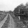 F3689<br /> Een zijsloot van de Zandsloot, kijkend richting Zandslootkade. Op dit terrein staan de woonhuizen van  de Diligence in de Postwijk. Het bollenbedrijf van de gebr. Doornbosch & Co staat aan het eind van het pad. Foto:1980
