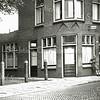 F0483 <br /> De kapperszaak en woonhuis van Jan de Jong aan de Hoofdstraat. Links de toegang naar de Ned.-herv. kerk of Dorpskerk en naar het Kuipershofje. Nu is hier het dorpsplein met parkeerplaatsen.