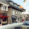 F0285 <br /> De Hoofdstraat in het centrum aan de westkant, maar nu gezien in noordelijke richting. Links de kruidenierswinkel van Van Goeverden (zie F0284) en verder de AMRO-bank, vroeger woonhuis en schilderswinkel van A. Vogelaar. Na een verbouwing (zowel inwendig als uitwendig) is hier nu Intertoys gevestigd. Voor de beschrijving van het hoekpand zie foto F0286. Verderop het plein voor de Ned.-herv. kerk (Dorpskerk) met de moderne bebouwing aan de Hortuslaan. Er hangt een spandoek van de SAMA: 'Koop met meer plezier'. SAMA stond voor: SAssenheimse Middenstands Acties. Foto: 1981.